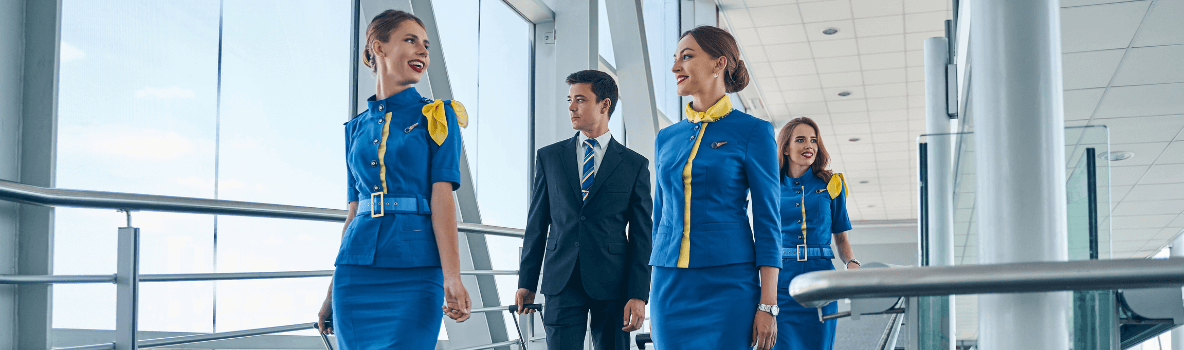 pilot and air hostesses walking through the airport